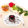 Chocolate cake, hot tea and red rose on a cloth decorated with hearts — Stock Photo #32297991