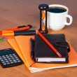 Organizer, exercise books, the handle, pencil, marker, cutter, calculator, hourglass and cup of coffee on a table — Stock Photo