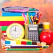 Books, alarm clock, pencil-case, a set of school accessories and an apple, on a table — Stock Photo