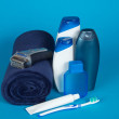 Towel, the razor, cosmetics, toothbrush and paste on a blue background — Stock Photo #32298125