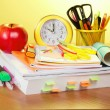 The book, a roll of exercise books, a support with handles, an alarm clock and red apple — Foto de Stock