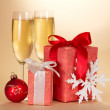 Wine glasses with champagne, christmas gift, christmas toy and snowflake on a beige background — Stock Photo