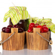 图库照片: Sweet cherries in buckets, and two banks with ready jam