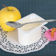 Box with yogurt, apple,soother and a napkin on blue background — Stock Photo