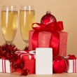 Christmas gifts, toys, tinsel, champagne and empty card, on a beige background — Stock Photo #32298843