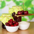 Two jars of jam, cup of sugar, wooden spoon with cherries, berries in a cup on a table — Stock Photo #32298875