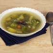 Plate of vegetable soup, spoon and blue napkin on a table — Stock Photo #32298937