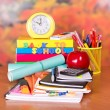 A set of school accessories, the calculator, alarm clock and red apple on a table — Stock Photo #32299103