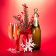 Champagne, fir-tree branch with tinsel, gift box, snowflake on a red background — Stock Photo