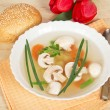 Plate with soup, a spoon, bread and red tulips on a beige napkin — Stock Photo #32299407