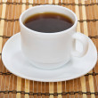 Cup of coffee with a saucer against a bamboo napkin — Stock Photo
