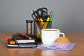 A office supply in a support hourglasses, a cup of coffee a spoon a napkin and cake on a table — Stock Photo