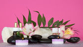 Candle, flower, stones with water decrease, before a howea leaf, on the pink — Stock Photo
