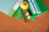The book, the folder, exercise books, a set of office tools and apple on a table — Stock Photo