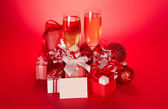 Wine glasses with champagne, gift boxes, Christmas spheres, snowflake and blank card on a red background — Stock Photo