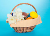 Wattled basket with white narcissuses, eggs and a napkin, on the blue — Stock Photo