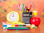 Alarm clock, writing materials, calculator, scissors, paints and an apple — Stock Photo