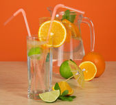 Jug, drink glass with straw, a citrus and an umbrella on a table — Stock Photo