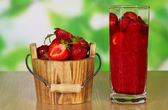 Bucket with strawberry and slices of berries in a glass, on a table — Foto Stock