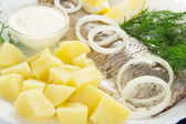 Herring and potatoes with sauce, onions a lemon and fennel, on a dish — Stock Photo