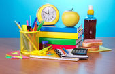 Books, an exercise book office supply alarm clock the calculator, apple, sandwich and a drink, on a table — Stock Photo