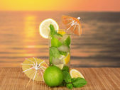 Green cocktail of alcohol with an umbrella, a lemon and spearmint, on a bamboo cloth against the sunset — Stock Photo