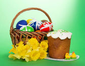 Yellow narcissuses, Easter cake, marzipan chickens and eggs in a basket, on a green background — Stock Photo