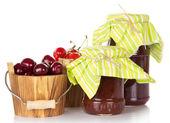 Diferentes graus de doce de cereja em baldes e frascos de compota isolado no branco — Foto Stock