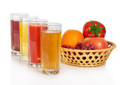 Set of juice in glasses and fruit, vegetables in a basket, isolated on white — Stock Photo
