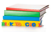 Pile of school textbooks and the plastic color letters — Stock Photo
