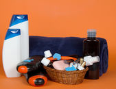Many different color tubes and bottles for hygiene, health and beauty on an orange background — Stock Photo