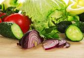 西红柿、 黄瓜、 洋葱、 白菜在菜板上 — 图库照片