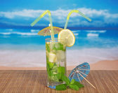 Fresh mojito, umbrella and spearmint leaf on a bamboo cloth, against the sea — Stock Photo