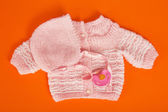 Nurseries a knitted jacket and a coif, and a pacifier on the orange — Stock Photo