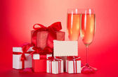 Two glasses of champagne, gift boxes with tapes and bows, empty card and petals of flowers on a red background — Stock Photo