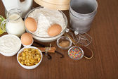 Milk, sour cream, flour, raisin and spices for an Easter cake, on a brown background — Stock Photo