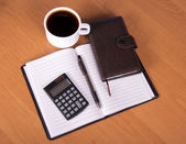 Open notepad, organizer the handle, the calculator and cup of coffee on a table — Stock Photo