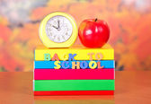 Pile of textbooks, red apple and alarm clock on a table — Stock Photo