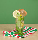 The mojito decorated with an umbrella and a lemon, mint, striped napkin on a table — Stock Photo