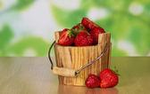 Cubo de madera de fresa madura fragante y dos bayas cerca de una mesa — Foto de Stock