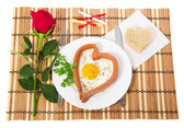 Sausage in the form of heart on a white plate, scrambled eggs and bread, notes with prediction, red rose — Stock Photo