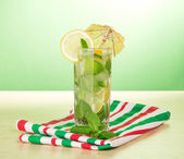 Cold drink with a lemon slice, spearmint, striped napkin, on a table — Stock Photo