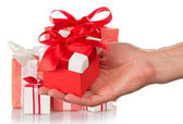 A lot of gift boxes and woman's hand holding a gift isolated on white — Stockfoto