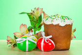 Easter cake, eggs and flowers on a table, on a green background — Stock Photo