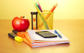 Exercise books, markers a support with handles a hourglass and apple — Stock Photo
