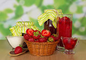 Jars of jam, cup with cream, basket with strawberry and spoon on a table — Stock Photo