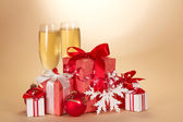 Two glasses with champagne, a set of gift boxes a snowflake and a Christmas toy on a beige background — Stock Photo