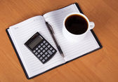 Open notepad, the handle, the calculator and cup of coffee on a table — Stock Photo