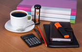 Notepad, organizer, marker, folders for documents the calculator, hourglasses and a cup of coffee on a table — Stock fotografie