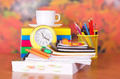 Books, cup with a saucer, a alarm clock and writing-materials on a table — Stock Photo